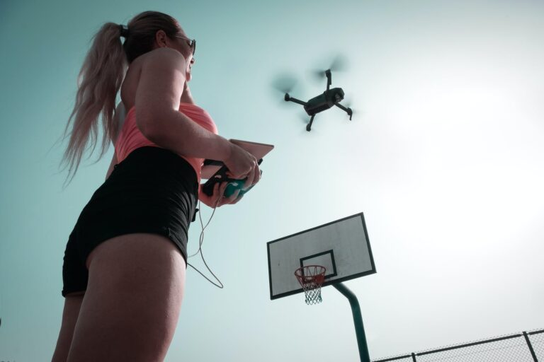 woman standing near basketball hoop controlling drone